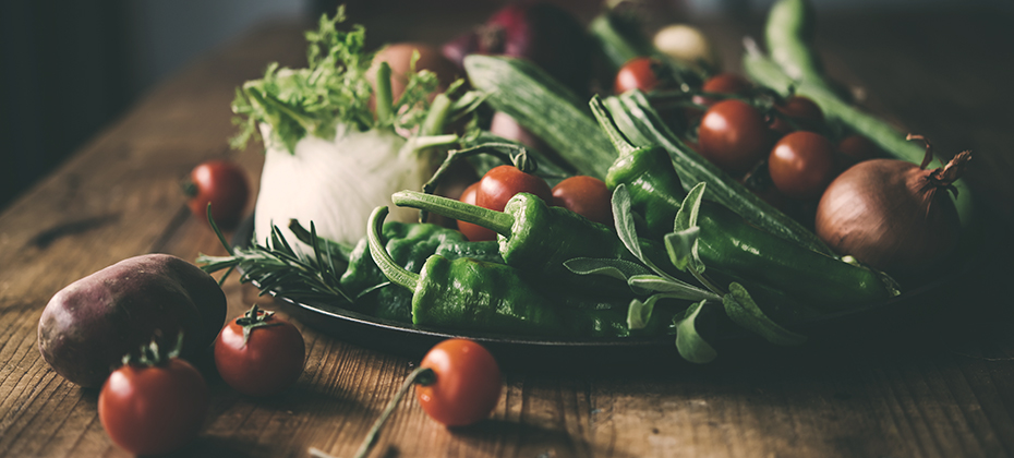 Summer vegetables on a wooden table: tomatoes, potatoes, fennel, onions, peppers, ...