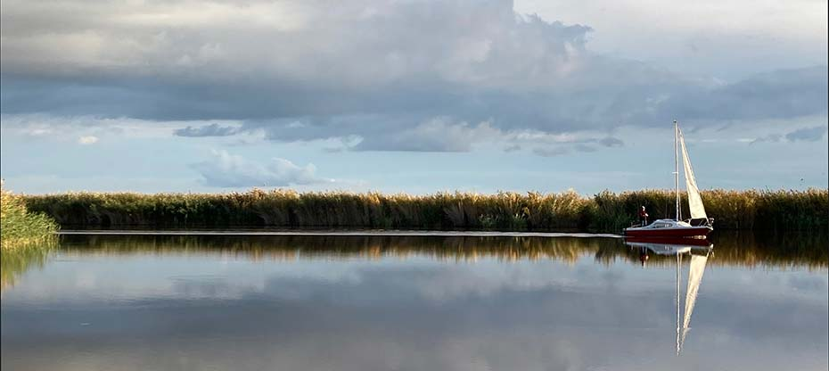 A sailing boat reflected in the autumnal Neusiedlersee